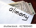 Small photo of Alimony written on an envelope with dollars.