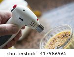 Stock photo a man is making a delicious dessert creme brulee with a gas torch the sugar is melted and 417986965