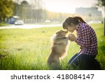 Stock photo young woman sitting with her dog sheltie on the grass and playing with the shetland sheepdog 418084147