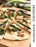 Small photo of Green asparagus and bacon tarte flambee or Flammkuchen, a typical Alsatian and South German dish, photographed on wooden board with natural light (Selective Focus, Focus one third into the image)