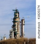 Detailed view of a distillation tower of a petrol refinery.Passenger jet in background. - stock photo