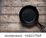 Small photo of Traditional cast iron skillet pan on vintage wooden table background. Kitchen equipment