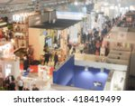 Small photo of Defocused background of a trade show with people visiting the commercial exhibition. Intentionally blurred post production for bokeh effect