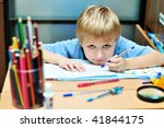 Small photo of left-handed boy doing a home task in own room
