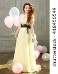 Small photo of Happy teen girl in prom look with helium air balloons