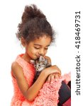 Small photo of Heartfelt photo of a four year old girl holding a kitten and closing her eyes while smiling