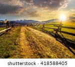 fence near the road through the  rural meadow in mountain region in spring time in evening light - stock photo