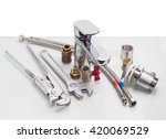 Small photo of Single handle mixer tap, plumber wrench, adjustable wrench, two hoses with metal braiding and another plumbing components on a reflective surface on a light background