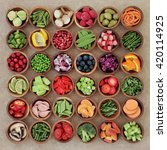 Small photo of Super food sampler for paleolithic diet with fresh vegetables and fruit in wooden bowls over brown paper background. High in vitamins, antioxidants, minerals and anthocyanins.