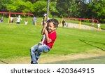 Smiling Asian Boy Swinging On ...