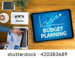 Small photo of BUDGET PLANNING Businessman working at office desk and using computer and objects, coffee, top view