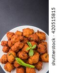 Small photo of Delicious Tasty and Yummy Indian Moong Dal vada or moong dal pakoda or moong vada or moong vade or Pakora (Fritter) with fried green chilli, red and green hot sauce.