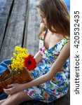 Small photo of Relaxation, rest, romanticism.The beautiful woman with a basket of flowers