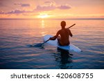 Silhouette Of Man Paddling On...