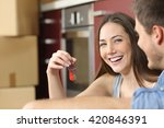 Small photo of Happy new flat couple of owners showing keys sitting in the floor of the kitchen while moving home