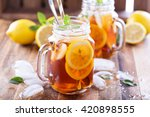 Stock photo iced tea with lemon slices and mint on rustic background 420898555