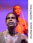 Small photo of Yirrganydji Aboriginal woman and men during cultural show in Queensland, Australia.
