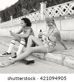 Small photo of Black and white view of ethnically diverse teenager girls friends together in suburban home exterior with white dog pet, using a smart phone, outdoors. Active adolescent women with animal on holiday.