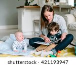 happy young mother reading a... | Shutterstock . vector #421193947