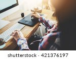 Stock photo young hipster girl sitting at her workspace and using modern computer and digital graphic tablet 421376197