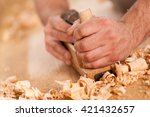 closeup of woodworker's hands shaving with a plane in a joinery workshop - stock photo