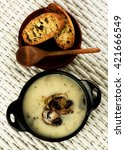 Small photo of Delicious Homemade Mushrooms Cream Soup Decorated with Roasted Champignons in Black Iron Stewpot with Herb Crunchy Bread and Wooden Spoon closeup on Wicker background