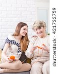 Small photo of Elderly woman knitting of orange yarn, accompanied by her granddaughter