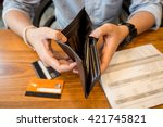 Small photo of credit card debt - holding an empty wallet.