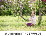 Woman meditates in the lotus position under a bush blooming lilac - stock photo