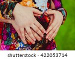 parents hands on the belly of... | Shutterstock . vector #422053714
