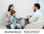 Mother and her son with funny face at the hospital talking to a doctor. - stock photo