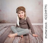 Small photo of cute little girl in airman hat sitting on wooden floor
