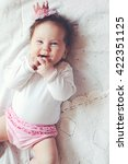 Small photo of Portrait of a 4 month cute baby girl wearing princess crown headband and lying down on a bed with polka dot white bedding, top view