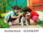 two girls playing with a beagle ...   Shutterstock . vector #422436349