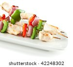 cubed chicken kabobs with red peppers, green peppers and red onion on isolated background - stock photo