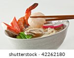 Seafood Udon Noodle Soup, Popular Japanese Dish, with shrimp, crabmeat, scallop, fish cake, snow peas, mushrooms in broth - stock photo