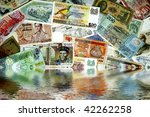 A mixture of various international paper currencies depicted as rising out of the ocean - stock photo