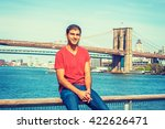 Small photo of Happy East Indian American man traveling in New York, wearing red V neck T shirt, jeans, sitting on fence by river, smiling. Manhattan, Brooklyn bridges on background. Instagram filtered effect.