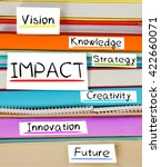 Small photo of Photo of colorful book stack with bookmarks and labels with IMPACT conceptual words