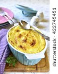 Small photo of Potato casserole with offal and vegetables in a baking form on a light background.