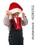 Smiling little boy looking to Christmas gift bag - stock photo