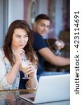 Small photo of Beautiful young woman in casual clothes sitting in street cafe with laptop and drink, playfully smiling aware of handsome guy looking at her with admiration from the next table