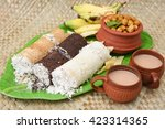 Small photo of Popular South Indian breakfast puttu / pittu made of wheat, ragi / finger millet, white rice flour and coconut, with chickpea / chana masala curry, banana, pappad / pappadom and tea, Kerala, India.