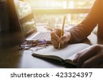 Stock photo young male student writes information from portable net book while prepare for lectures in 423324397