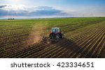 tractor cultivating field at...