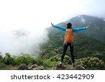 cheering woman hiker open arms... | Shutterstock . vector #423442909
