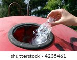 Female hand throwing empty plastic bottle into slot of waste separation container - stock photo
