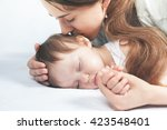 mother kissing a baby. care... | Shutterstock . vector #423548401