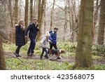 Stock photo side view of family walking pet dog in a wood closer in 423568075