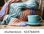 Small photo of A turquoise cup and saucer sits by a coordinating knit afghan and blanket.